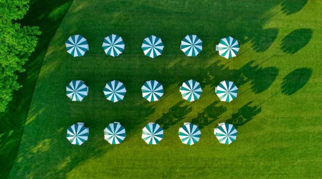 Three rows of five tables covered by green and white umbrellas. All perfectly spaced.