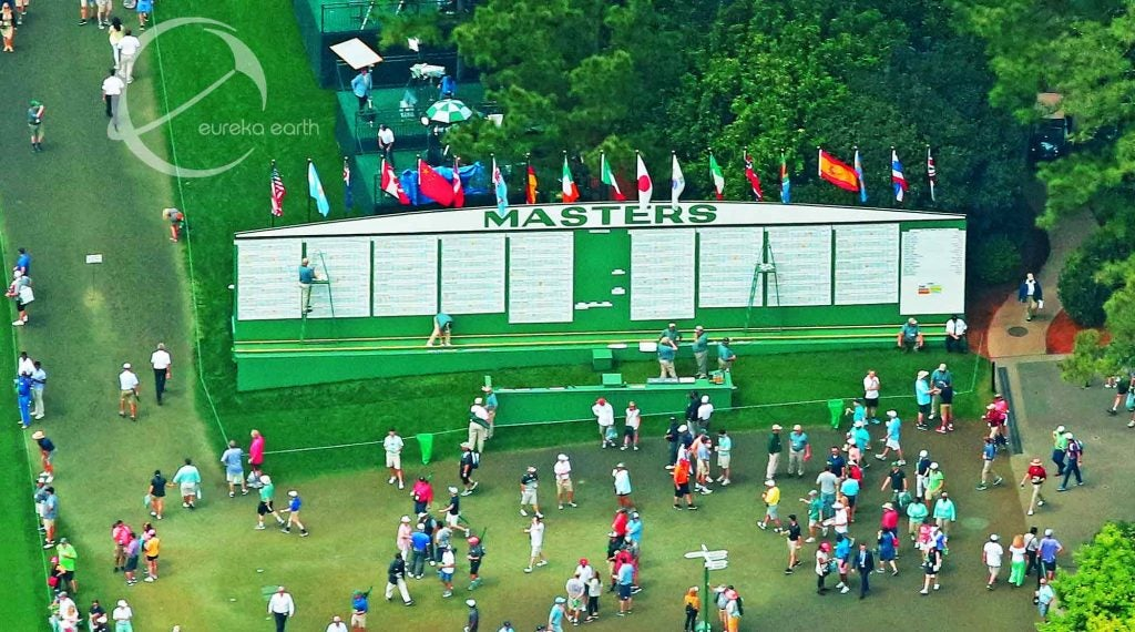 Patrons congregate by the leaderboard next to the 1st fairway.