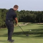 Golf instructor swings driver