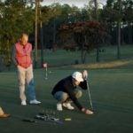 Two men watch a golfer putt
