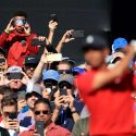 Fans photograph Tiger Woods playing golf