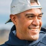 Tony Finau smiles at a golf course.