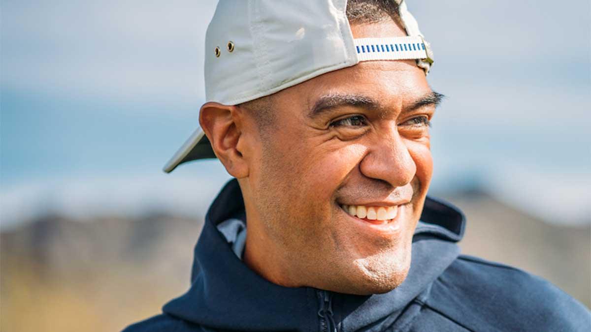 Tony Finau smiles at a golf course.