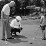 President Dwight Eisenhower watches grandson David putt at Camp David.