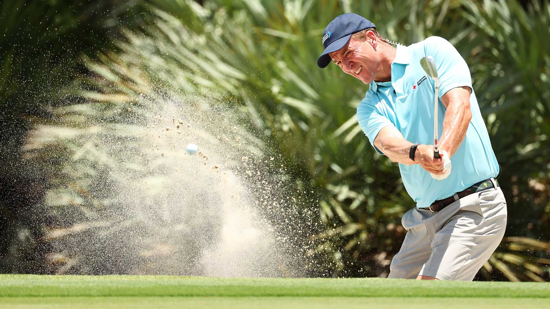 Peyton Manning hits out of a sand trap during a practice round on Saturday.