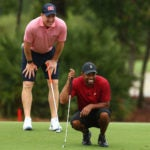 Tiger Woods and Peyton Manning line up a putt.