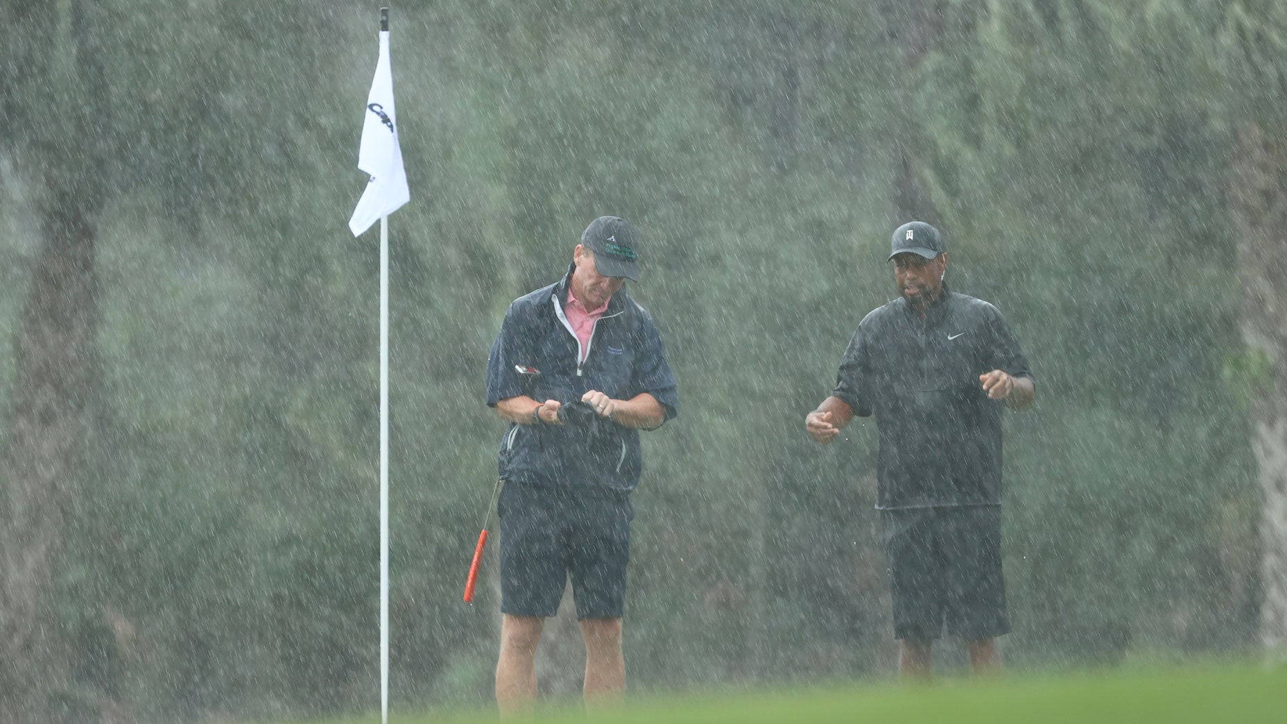 Peyton Manning and Tiger Woods battle the rain on the 13th green at Medalist Golf Club.