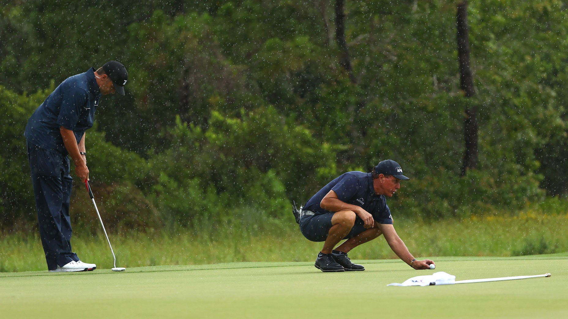 Phil Mickelson lines up a putt as Tom Brady looks on on the 12th green at Medalist Golf Club.