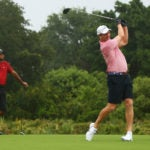 Peyton Manning hits a tee shot as Tiger Woods watches on