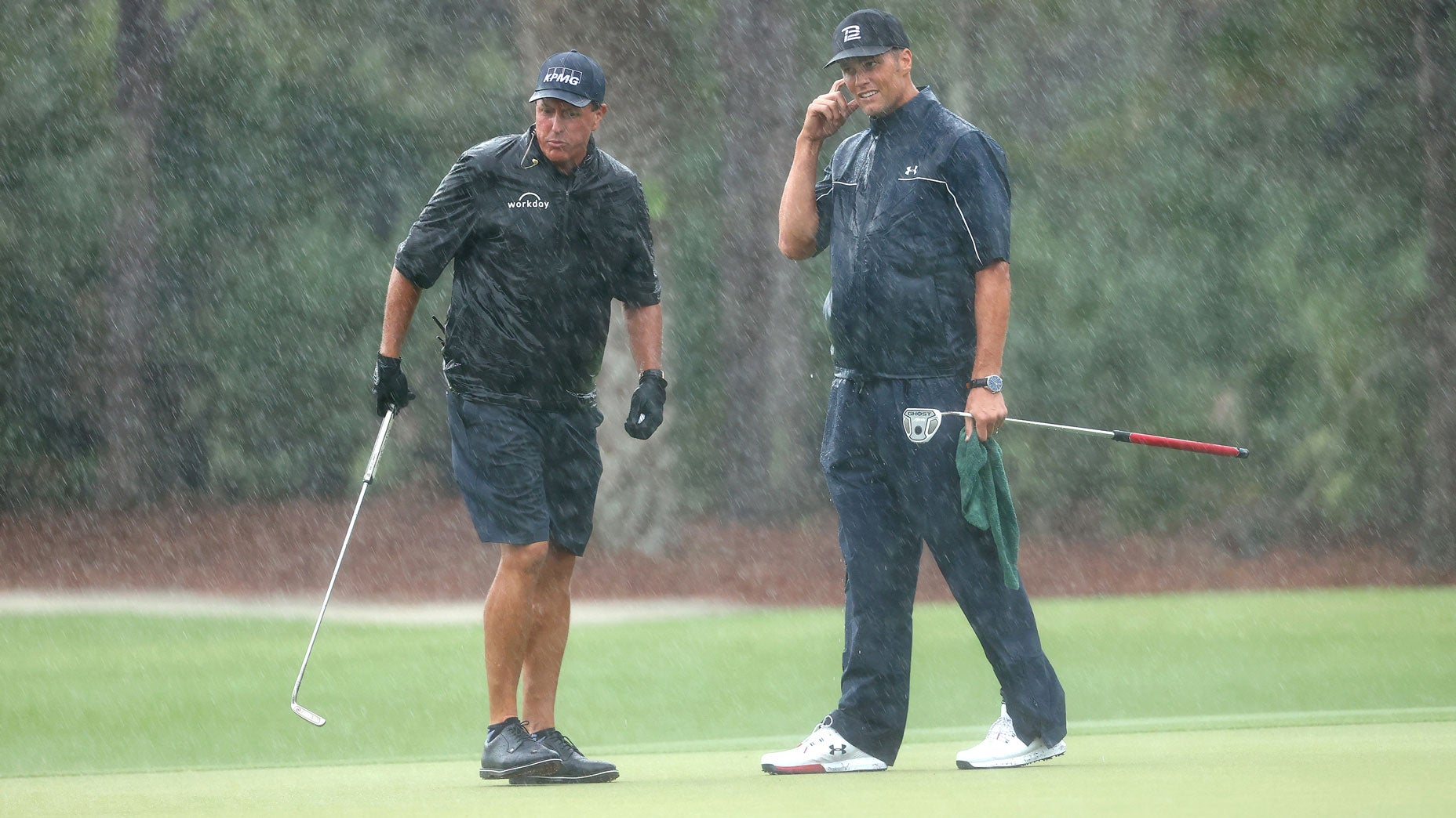 Phil Mickelson and Tom Brady stand in the rain on the 13th green at Medalist Golf Club.