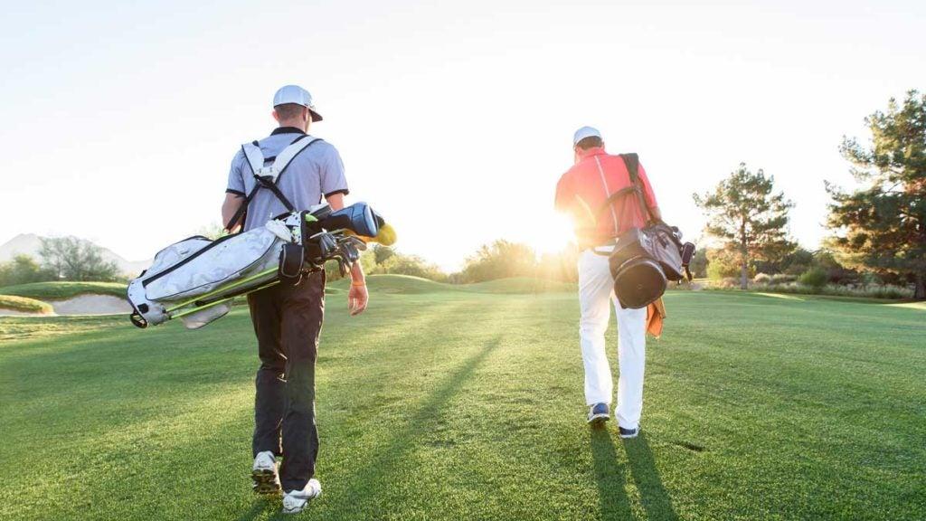 men carrying golf bags