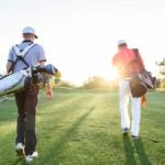 men carrying golf bags