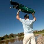 Man throwing golf cart into lake