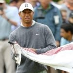 Tiger Woods cleans golf club