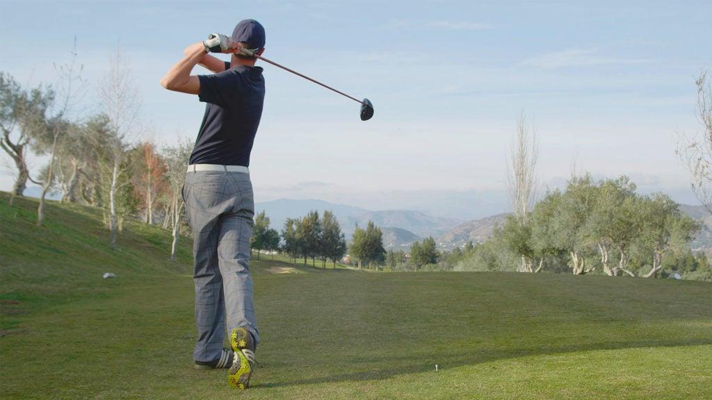 A golfer takes a swing.
