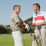 Two golfers talk on the golf course.
