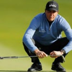 Phil Mickelson crouches on putting green