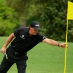 Phil Mickelson reaches for a flagstick