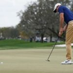 Pro golfer Rory McIlroy putts on golf green