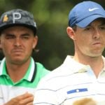 Rickie Fowler and Rory McIlroy watch golf ball
