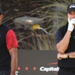 Tiger Woods and Phil Mickelson watch golf shot