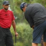 Tiger Woods watches Phil Mickelson putt on golf green