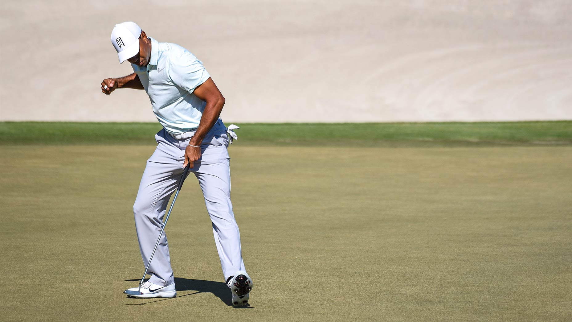 Tiger Woods pumps his first after making a putt.