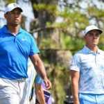 Tiger Woods and Rickie Fowler walk off the tee box.