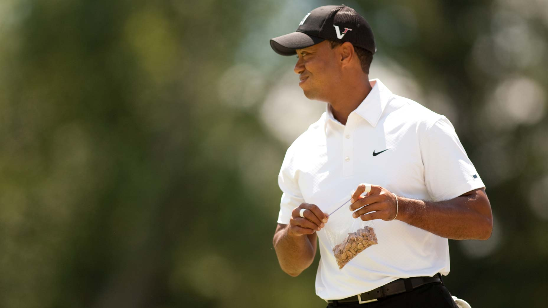 Tiger Woods eats a snack during a round.