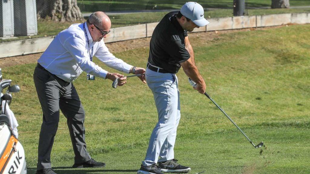 coach helps golfer on range