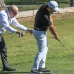 coach helps golfer on range