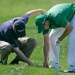 Two golfers look for golf balls.