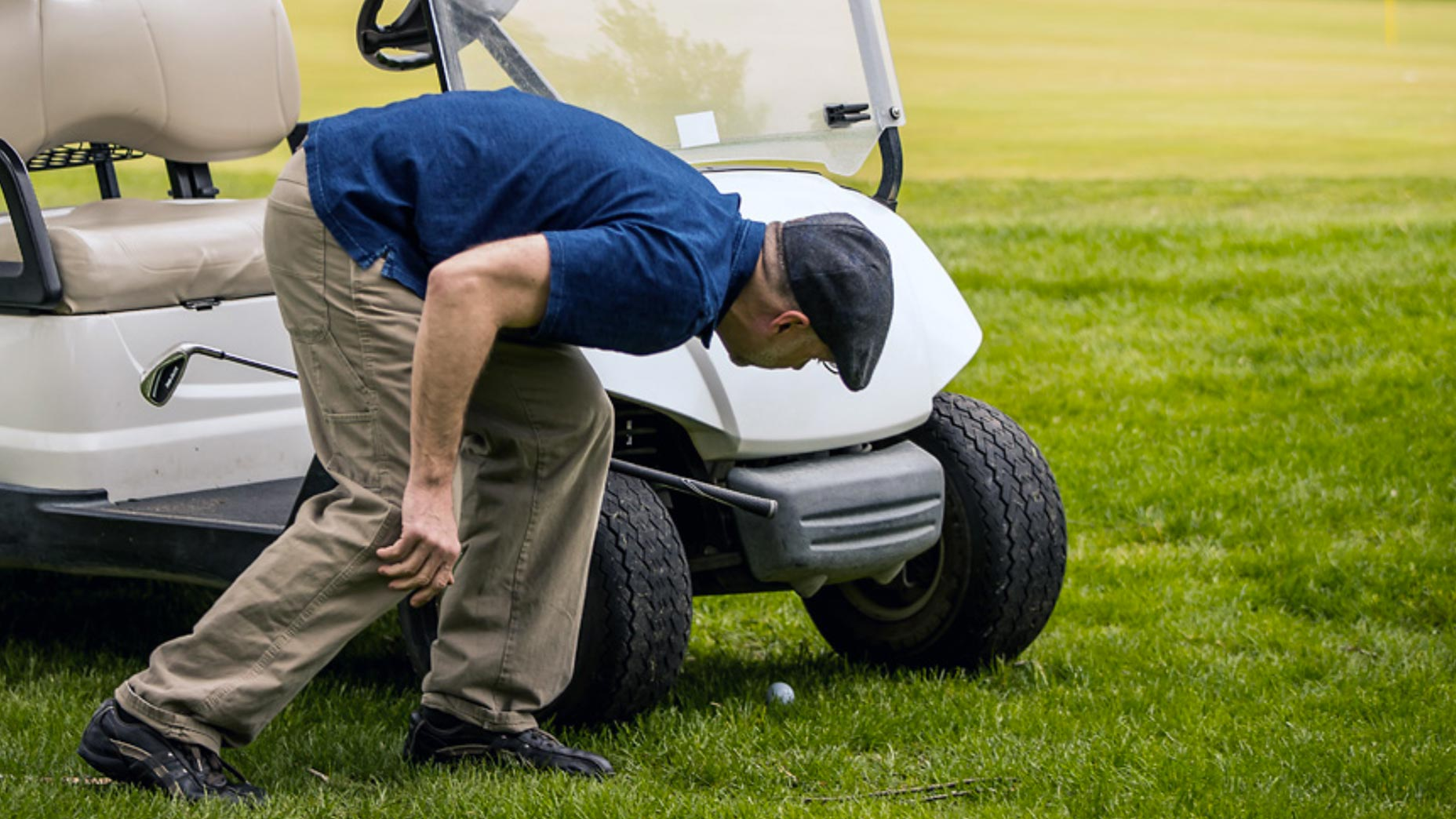 A man looks for his golf ball under a cart.