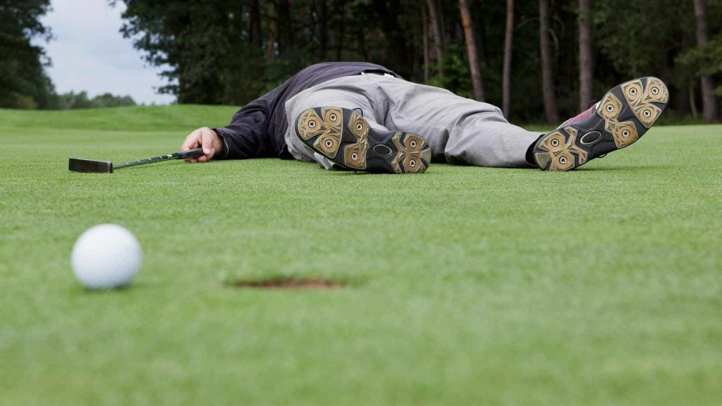 Golfer laying on the green.