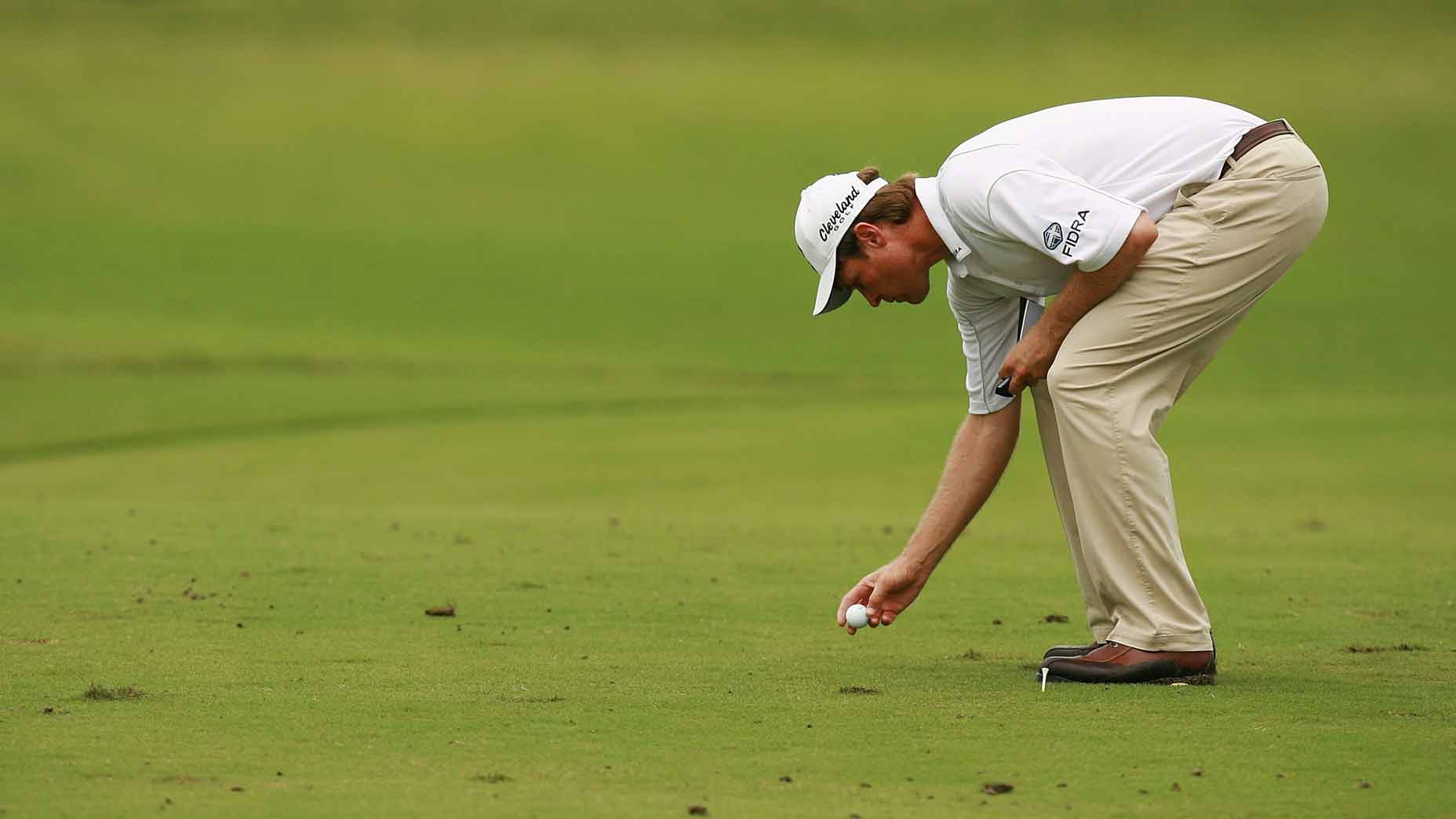 Golfer replacing ball in fairway