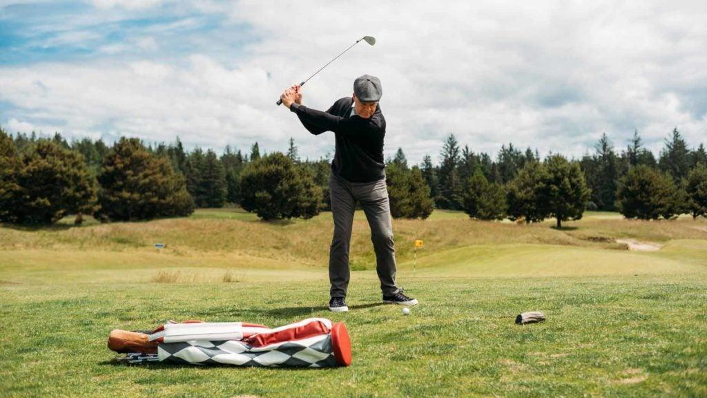 Todd Rohrer swinging next to Macdonald golf bag
