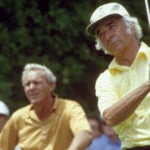 Bud Chapman tees off as Arnold Palmer looks on.