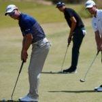 three golfers putting