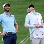 Pro golfer Dustin Johnson and caddie laugh