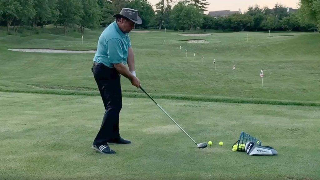Golf instructor demonstrates drill