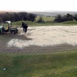 Sand being poured on golf greens.
