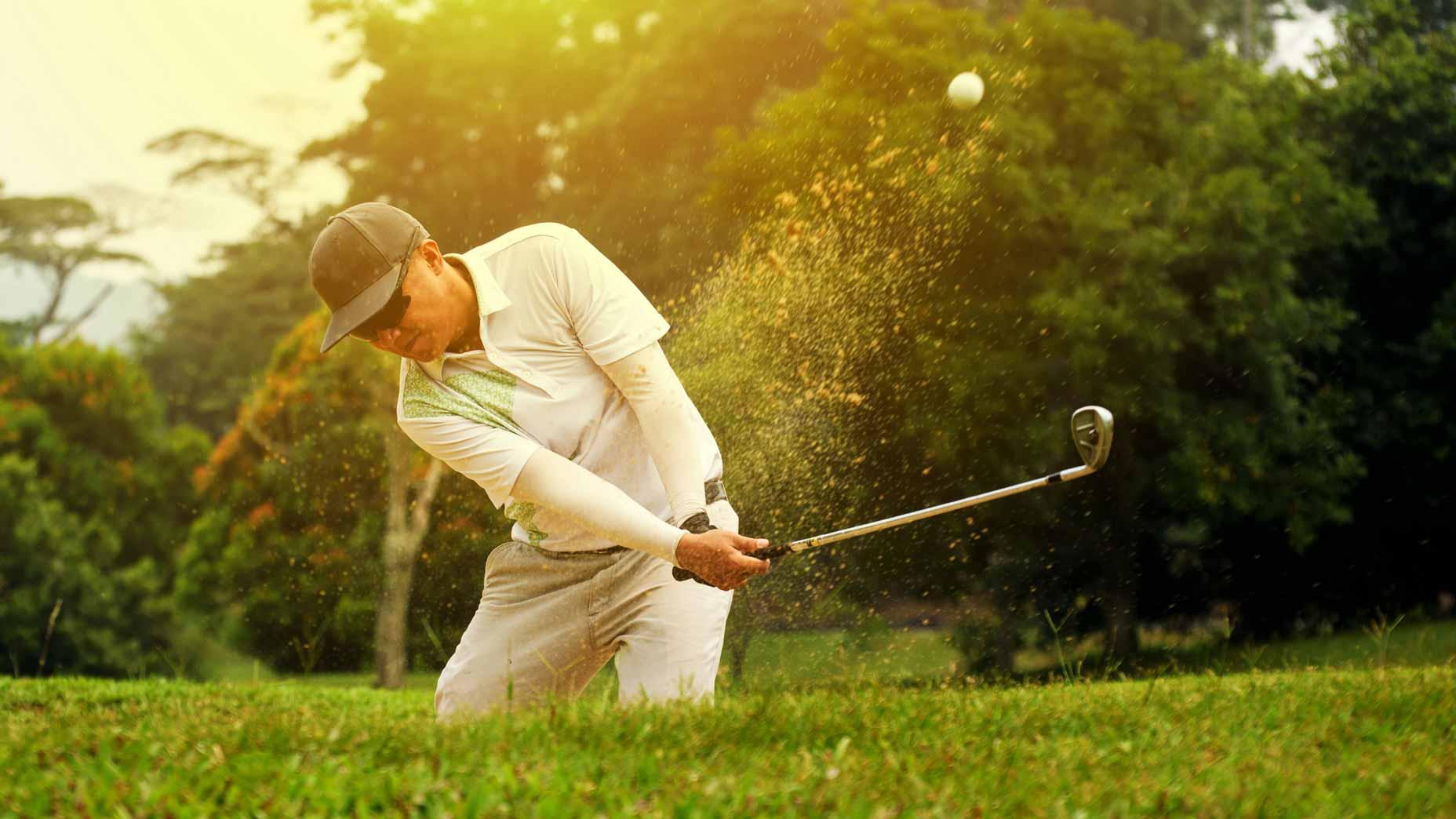 golfer hits bunker shot