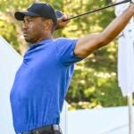 Tiger Woods stretches his back and shoulders before a round.
