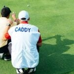 A golfer and caddie read a putt.