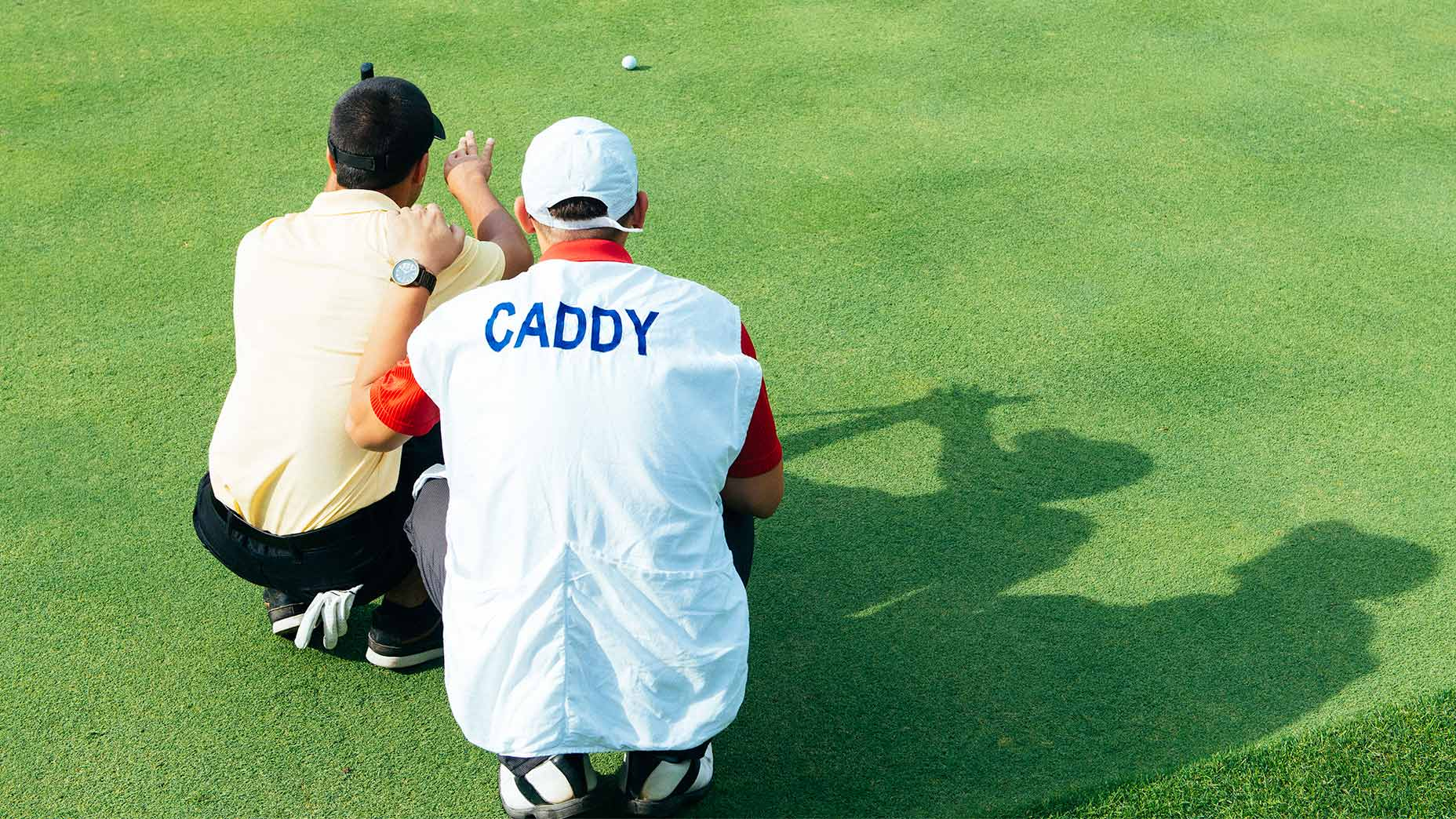 A golfer and caddie read a putt.