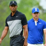 Tiger Woods and Brooks Koepka on the golf course.