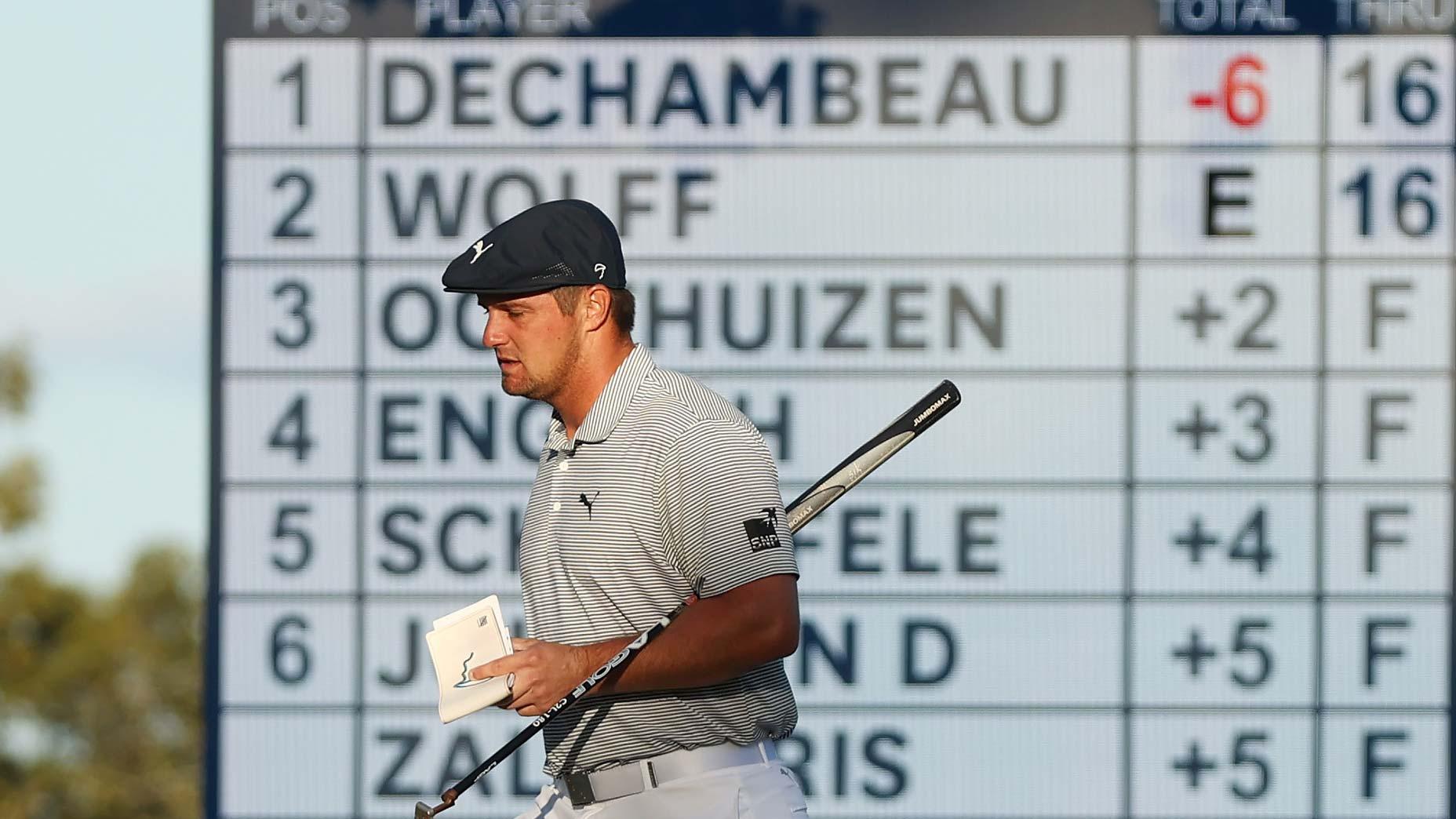 bryson dechambeau walks with scoreboard