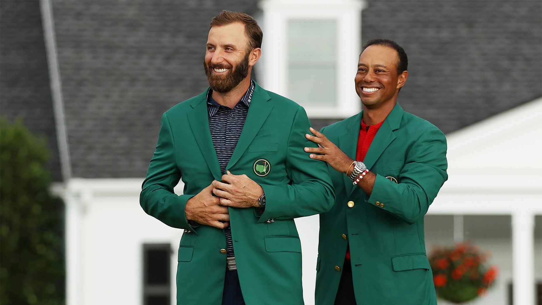 Tiger Woods puts the green jacket on Dustin Johnson.