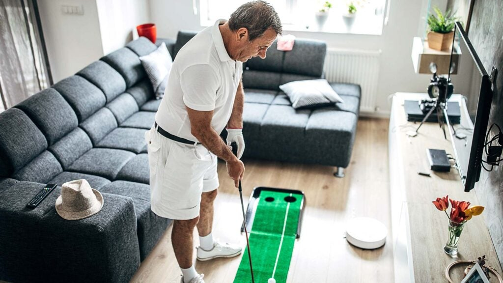 man practicing golf at home