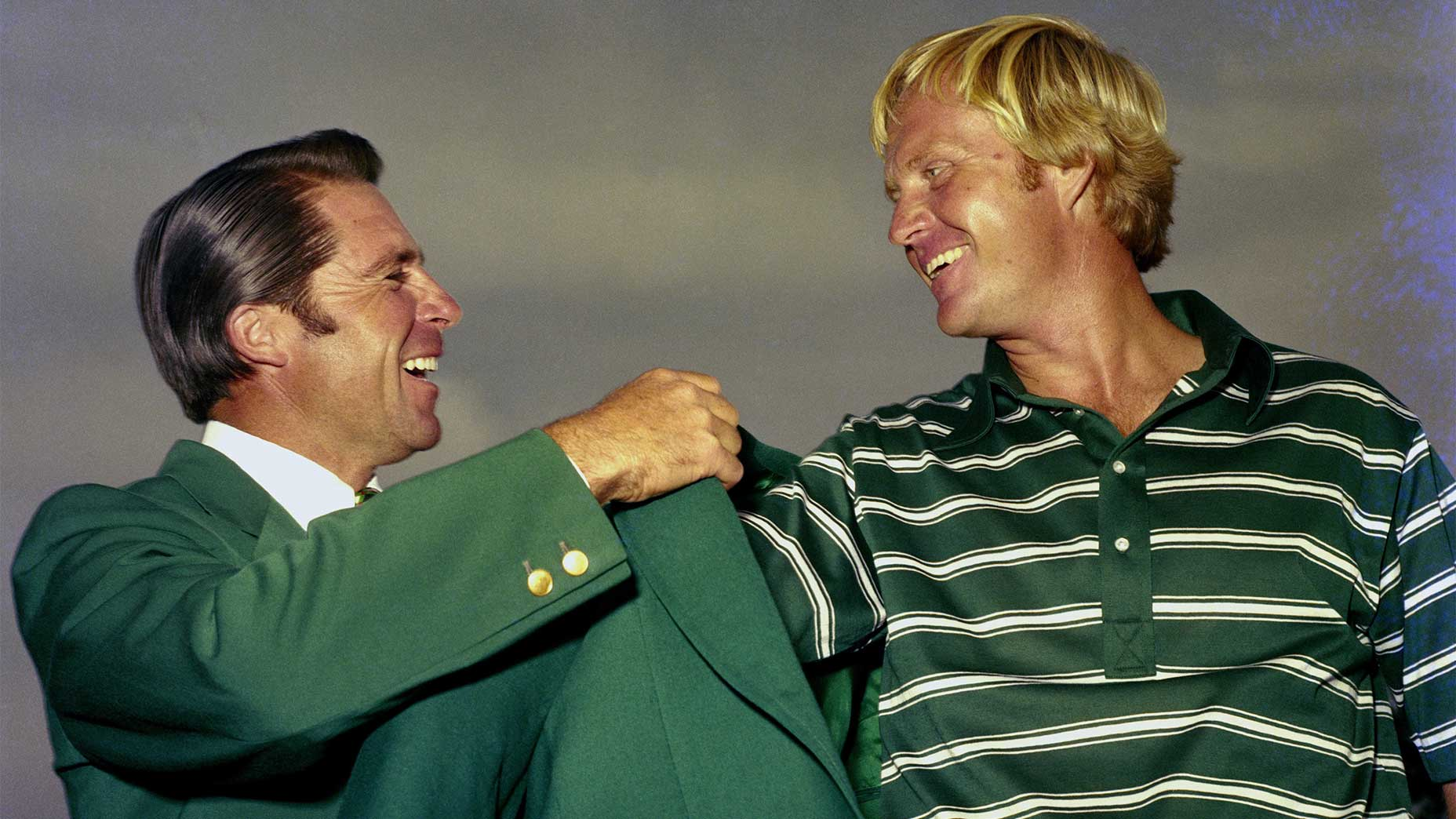 Gary Player puts the Masters green jacket on Jack Nicklaus in 1975.